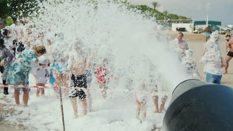 A-Crowd-Of-Vacationers-Have-Fun-On-The-Beach-Under-The-Streams-Of-Foam-Foam-Party-On-The-Beach-Enter