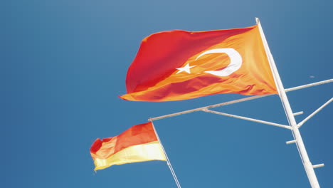 The-Turkish-Flag-And-The-Flag-Of-The-Rescue-Service-Are-Fluttering-Against-The-Blue-Sky-Safe-Rest-Co