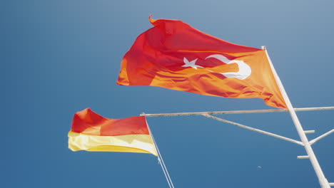 Red-With-Crescent-Turkey-Flag-And-Rescue-Service-Flag-Against-The-Blue-Sky-Beach-Season-In-Turkey