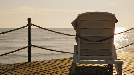 Lounge-For-Relaxation-Is-On-The-Pier-Turned-To-The-Rising-Sun-Over-The-Sea-4k-Video