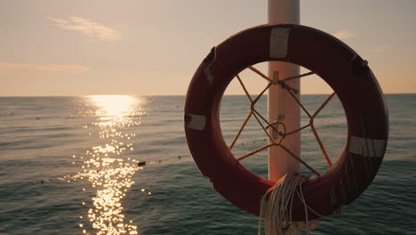 Lifebuoy-Hanging-On-The-Background-Of-The-Sea-At-Sunrise-Morning-At-The-Sea-4k-Video