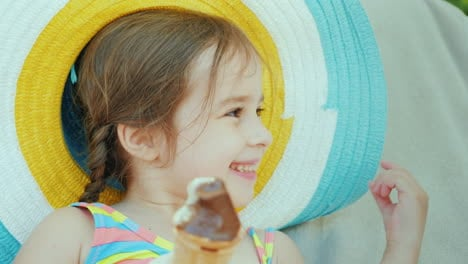 A-Cheerful-Girl-In-A-Hat-Eats-Ice-Cream-Relaxation-At-The-Resort-With-Children-4k-Video