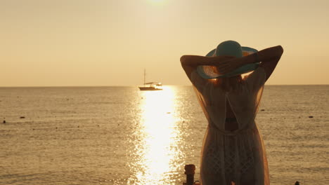 A-Young-Woman-In-A-Light-Dress-And-Hat-Meets-The-Dawn-At-The-Sea-A-Ship-Is-Visible-In-The-Distance-D