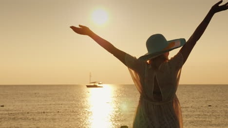 A-Young-Woman-Enjoys-The-Sunrise-Over-The-Sea-Emotionally-Waving-Her-Hands-A-Ship-Is-Visible-In-The-
