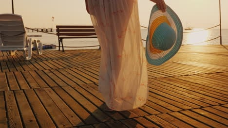 A-Woman-Walks-The-Pier-Towards-The-Rising-Sun-In-The-Picture-You-Can-See-A-Hand-With-A-Hat-Travel-An