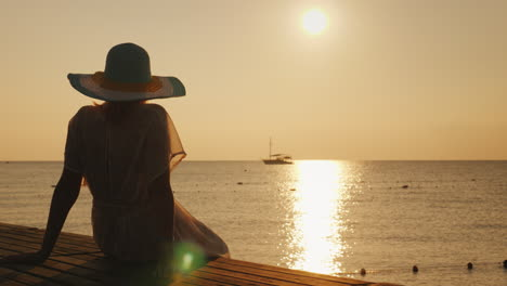 A-Young-Woman-Meets-The-Sunrise-On-The-Pier-He-Sits-And-Looks-At-The-Sun-And-The-Ship-In-The-Sea-Dre