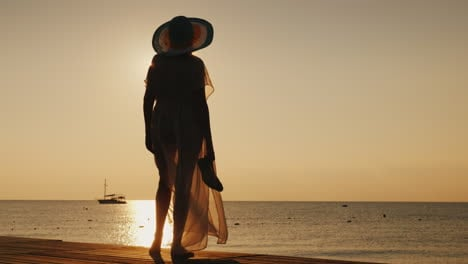 A-Stylish-Girl-In-Fluttering-Clothes-And-A-Broad-Brimmed-Hat-Meets-The-Sunrise-On-A-Sea-Pier