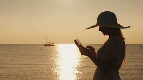 Silhouettes-A-Young-Woman-In-A-Wide-Brimmed-Hat-That-Uses-A-Tablet-Against-The-Backdrop-Of-A-Beautif