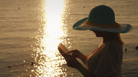 A-Young-Girl-In-A-Hat-Uses-A-Tablet-Against-The-Backdrop-Of-The-Rising-Sun-On-A-Sea-Pier-Top-View