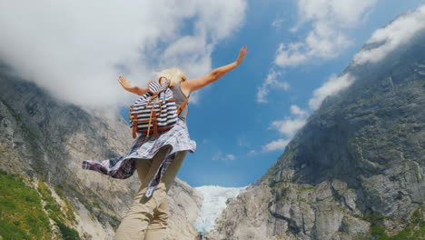 A-Healthy-Woman-Raised-Her-Hands-Joyfully-Standing-On-The-Background-Of-The-Brixdal-Glacier-In-Norwa