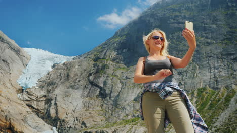 An-Attractive-Woman-Takes-A-Picture-Of-Herself-Against-The-Background-Of-The-Mountains-And-The-Glaci
