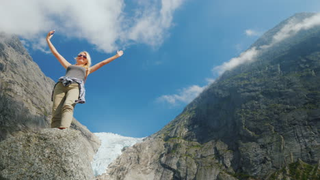 A-Successful-Young-Woman-Photographes-Herself-Against-The-Backdrop-Of-Mountains-And-A-Glacier-In-Nor