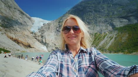 A-Happy-Woman-Is-Shooting-A-Selfie-Video-On-A-Background-Of-Mountains-And-A-Glacier-On-Top-Journey-T