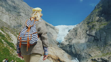 A-Woman-In-Warm-Clothes-Admires-The-Glacier-High-In-The-Mountains-Briksdal-Glacier-In-Norway-A-Trip-