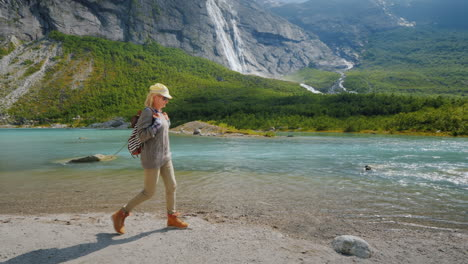 A-Tourist-Woman-Walks-Alone-Surrounded-By-Majestic-Nature---Mountains-With-Waterfalls-On-Top-The-Tra