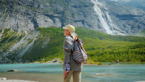 The-Traveler-Walks-Among-The-Majestic-Cliffs-With-Waterfalls-And-Glaciers-On-Top-Traveling-In-Norway
