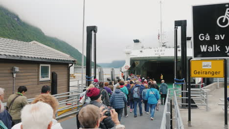Buses-Cars-And-Tourists-Leave-The-Ferry-At-The-Shore-Of-The-Fjord-A-Group-Of-Other-People-And-Transp