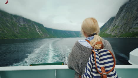 Tourist-Woman-Admiring-The-Picturesque-Norwegian-Fjord-From-The-Stern-Of-A-Cruise-Ship