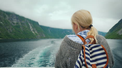 A-Woman-Stands-At-The-Stern-Of-A-Cruise-Ship-Looks-At-The-Retreating-Rocks-And-Waves-Of-The-Fjord