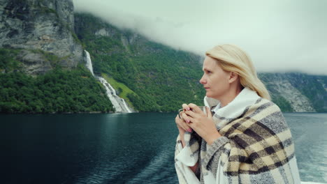 A-Woman-With-A-Cup-Of-Tea-In-Her-Hands-Aboard-A-Cruise-Ship-Looks-At-The-Beautiful-Mountains-Of-The-