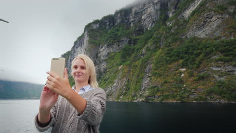 A-Woman-Takes-Pictures-Of-Herself-Against-The-Backdrop-Of-The-Norwegian-Fjord-Travelling-On-A-Cruise