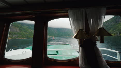 Cruise-On-The-Picturesque-Fjord---View-From-The-Window-Of-The-Ship-A-Norwegian-Flag-Is-Visible-4k-Vi