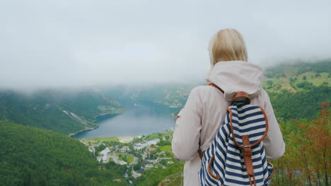 A-Woman-With-A-Backpack-Admires-A-Beautiful-View-Of-The-Fjord-View-From-The-Famous-Flying-Rock-In-No