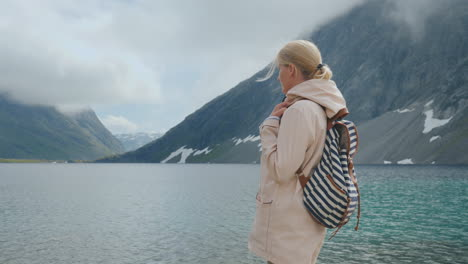 A-Woman-Looks-At-A-High-Altitude-Lake-In-Norway-Seclusion-And-Run-Away-From-The-Whole-Concept-4k-Vid