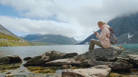 A-Traveler-Uses-A-Smartphone-High-In-The-Mountains-Near-The-Highland-Norwegian-Lake-Successful-Woman