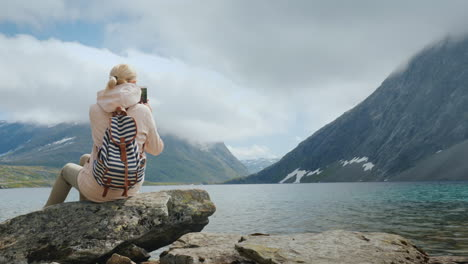 A-Woman-Takes-A-Picture-Of-A-Scenic-View-Of-A-High-Mountainous-Norwegian-Lake-Holidays-At-The-Edge-O