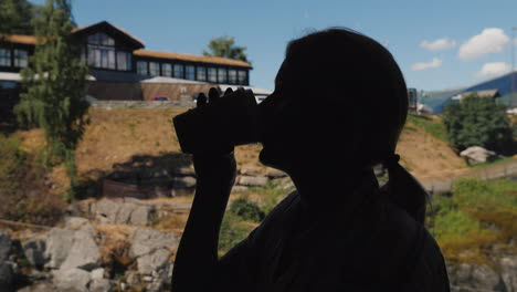 Silhouette-Of-Woman-Drinking-Coffee-By-The-Window-Sits-In-A-Cafe-High-In-The-Mountains-Of-Norway