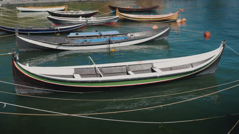 Several-Small-Wooden-Boats-Moored-At-The-Shore-Of-A-Fishing-Village-4k-Video