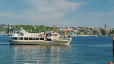 A-Small-Cruise-Ship-With-Tourists-Floating-On-The-Background-Of-The-City-Line-Of-Oslo