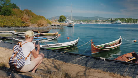 A-Woman-With-A-Backpack-Sits-On-The-Waterfront-Of-The-City-Of-Oslo-In-Norway-Near-The-Fishing-Boats-