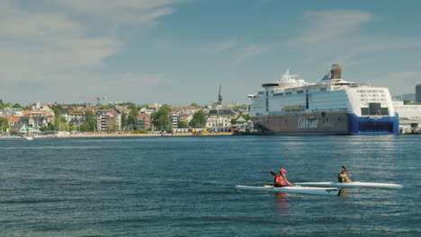 A-Pair-Of-Rowers-Swim-In-A-Kayak-Against-The-Background-Of-The-Oslo-City-Line