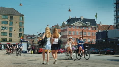 A-Lively-Street-In-The-Central-Part-Of-Copenhagen-Along-A-Bicycle-Path-A-Group-Of-Cyclists-Rides-Wal
