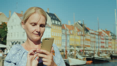 A-Happy-Woman-Uses-A-Smartphone-Stands-On-The-Background-Of-The-Canal-And-The-Popular-Tourist-Street