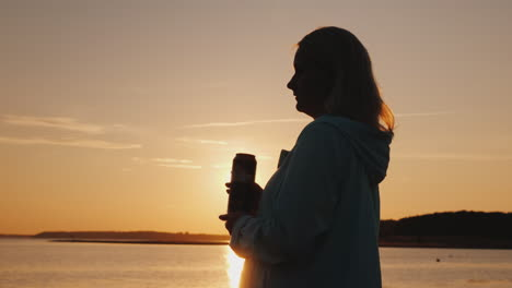 Lonely-Woman-Drinks-Beer-From-A-Can-On-The-Lake-Standing-Alone-By-The-Fence-Looking-At-The-Sunset