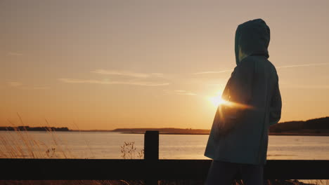Lonely-Woman-Silhouette-Sitting-By-The-Fence-Admiring-The-Sunset-Over-The-Lake