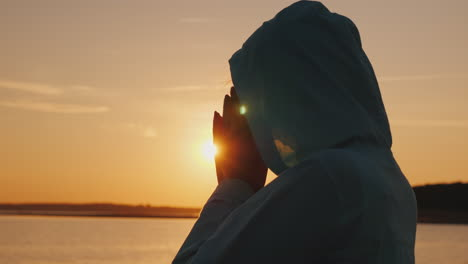 A-Middle-Aged-Woman-In-A-Hood-Praying-Near-The-Lake-At-Sunset