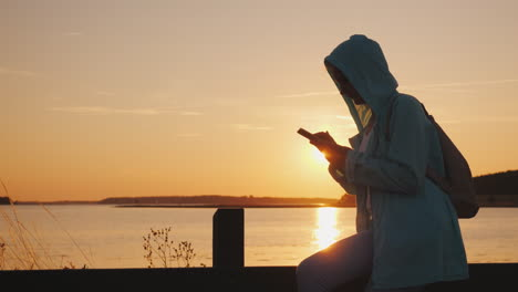 A-Woman-In-A-Hood-Sits-On-A-Fence-Near-A-Picturesque-Lake-Uses-A-Smartphone-Beautiful-Sunset