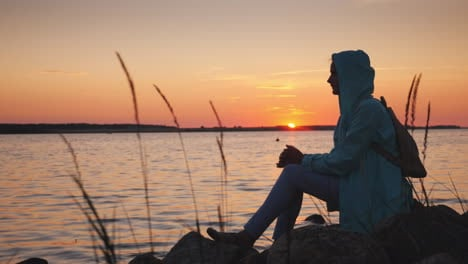 Woman-Sits-On-A-Rock-Near-A-Picturesque-Lake-At-Sunset