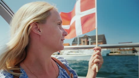 A-Tourist-With-The-Flag-Of-Denmark-Sails-On-A-Sightseeing-Boat-Through-The-City-s-Canals