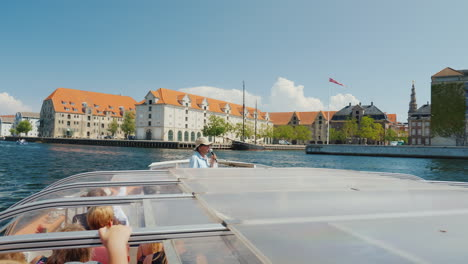 Tour-Through-The-Canals-Of-Copenhagen-A-Boat-With-Tourists-Sailing-Along-A-Narrow-Canal-Ahead-Of-The