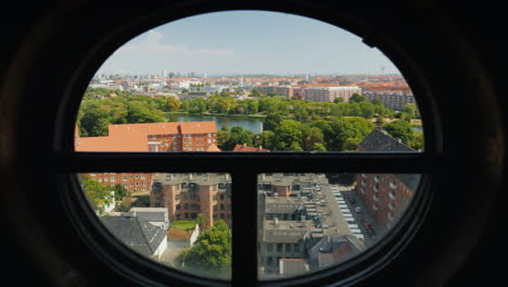 View-Of-The-City-Of-Copenhagen-Through-The-Ancient-Round-Window-Of-The-Screw-Tower-4k-Video