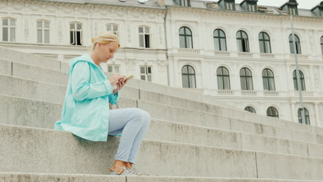 A-Woman-Uses-A-Smartphone-Sits-On-The-Steps-Against-The-Background-Of-A-Beautiful-Building-A-Trip-Th