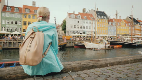 A-Woman-Sits-On-The-Embankment-And-Admires-The-Colorful-Buildings-On-The-Banks-Of-The-Nyhavn-Canal-I