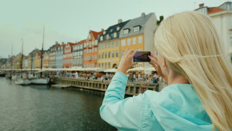 A-Woman-Strolls-Along-The-Canal-Against-The-Background-Of-Famous-Colorful-Houses-The-Most-Popular-Pl