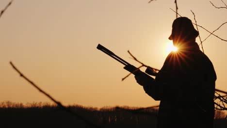 Silhouette-Of-A-Hunter-With-A-Gun-The-Sun-s-Rays-Shine-In-His-Face
