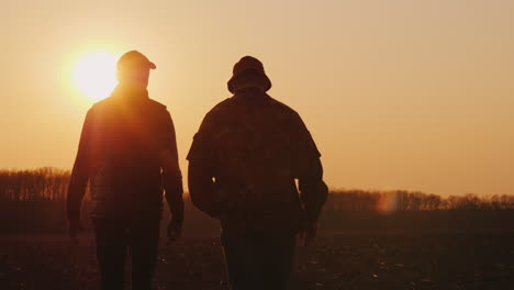 Farmers-Father-And-Son-Walk-Across-The-Field-At-Sunset-Chatting